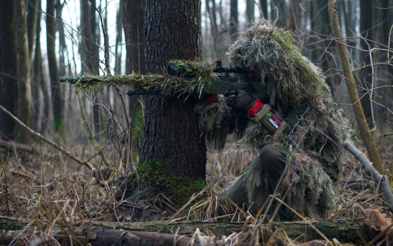 a soldier sniper aiming though the rifle scope in forest